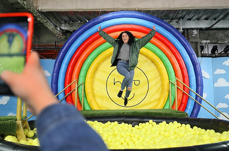 A woman mid-air jumping into a ball pit filled with yellow balls backed by a circular rainbow backdrop.