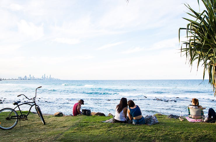 Two young women sit on a picnic rug with their backs to us and are leaning in looking at something on their phones. They overlook the beach at Burleigh Heads, with a Gold Coast cityscape in the distance.
