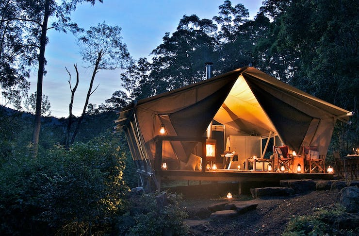 a beautiful scene at night, a glamping tent glows.