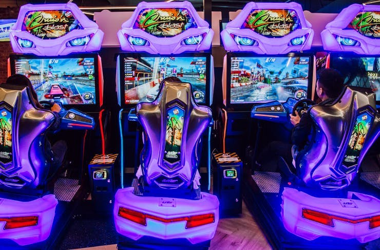 A row of virtual racing car games, drenched in a purple neon light.