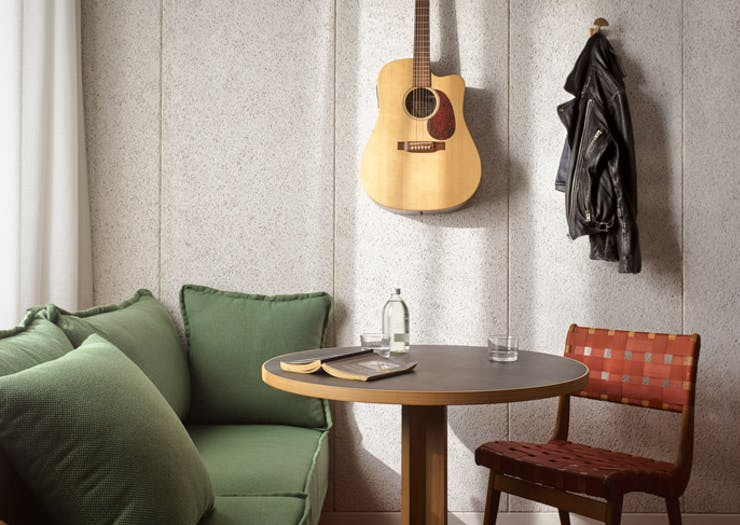 A green lounge, guitar and cafe table at Ace Hotel Sydney