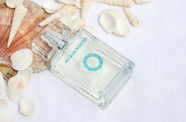 A close-up of a bottle of perfume that says 'Acqua Noosa' among scattered sea shells.