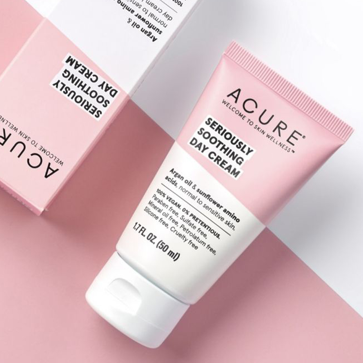 a tube of Acure cream on a pink and white background