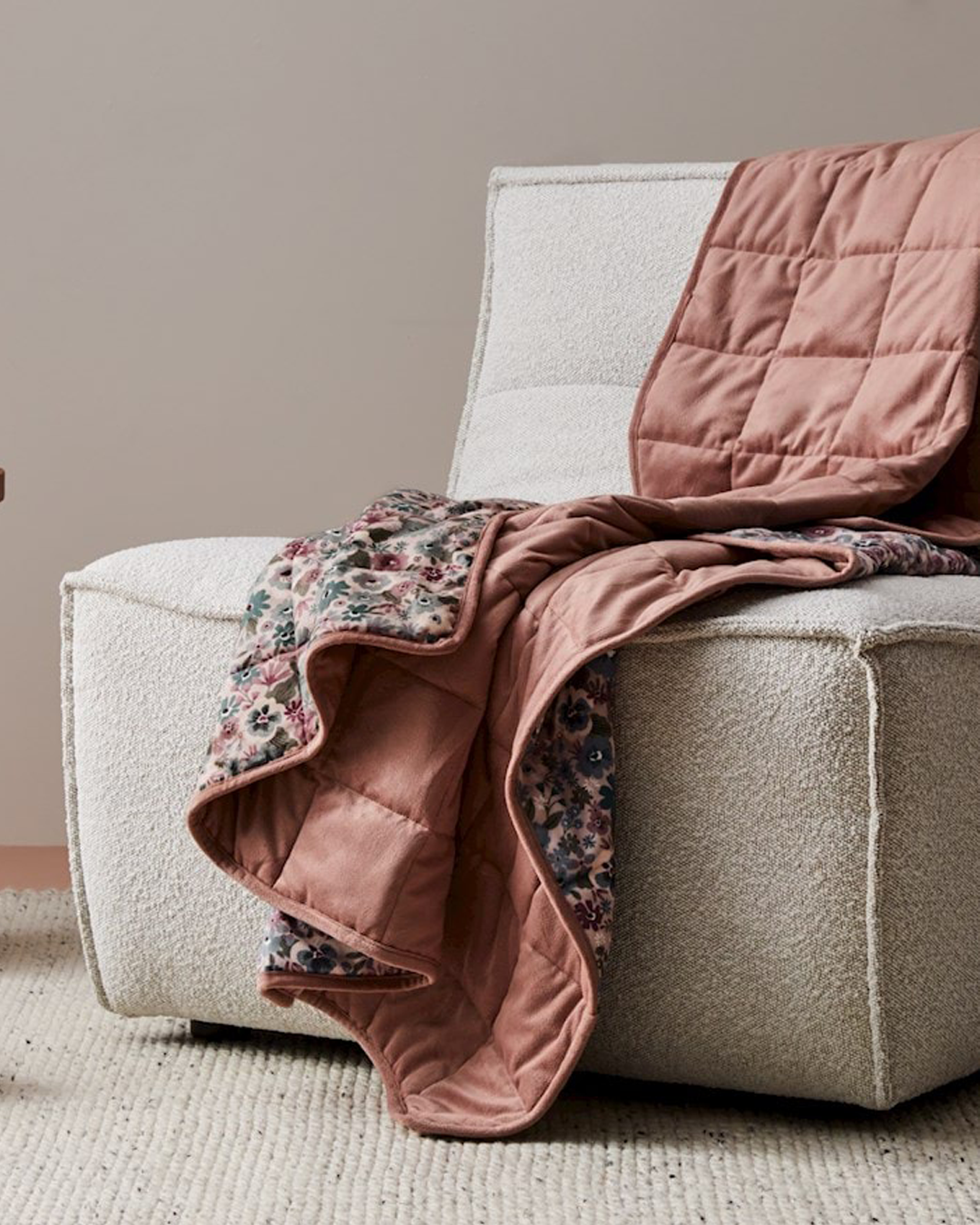 A pink and floral blanket draped over a sofa.