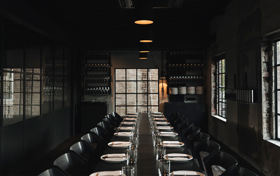 a dark room with a long table inside, and wine bottles on the wall at the end