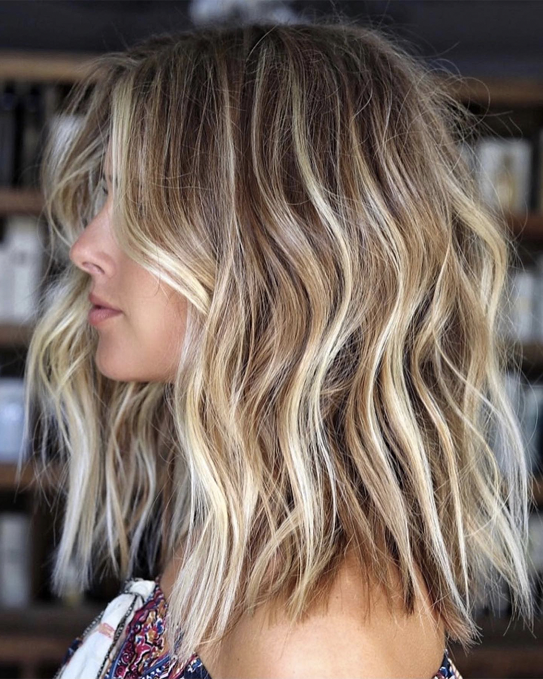 A blonde woman stands side on with hair done by Amiee Marie.