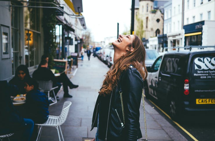 Young woman in a leather jacket on a busy street smiling and looking up at the sky.