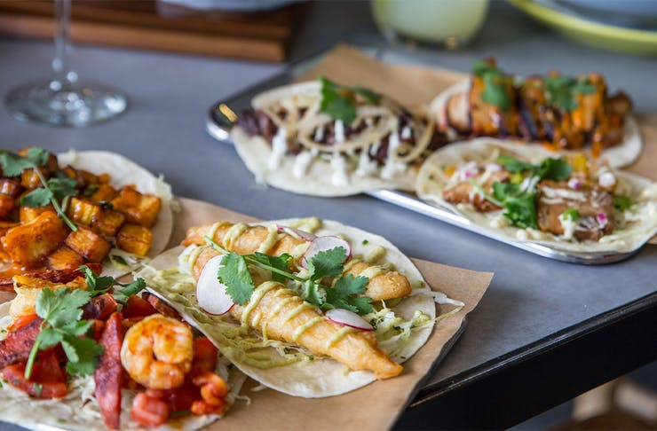 Two boards piled with tacos
