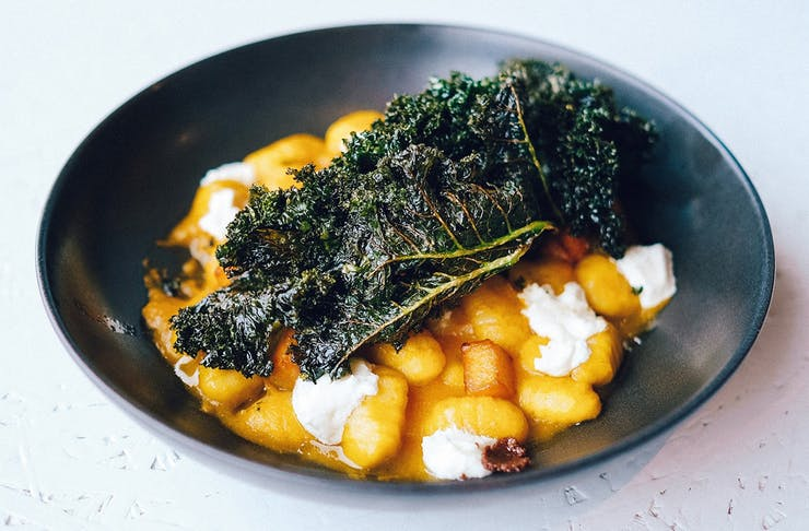 a bowl of gnoochi topped with kale