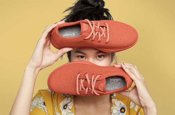 A girl holds up a red pair or Allbirds in front of a yellow background