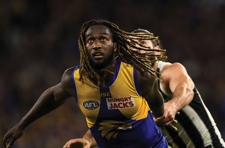 Nic Naitunui from the West Coast Eagles has eyes on the ball as he is chased by a Collingwood player.