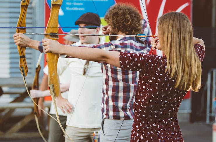 A girl lines up a shot with a bow and arrow at anti valentine's day