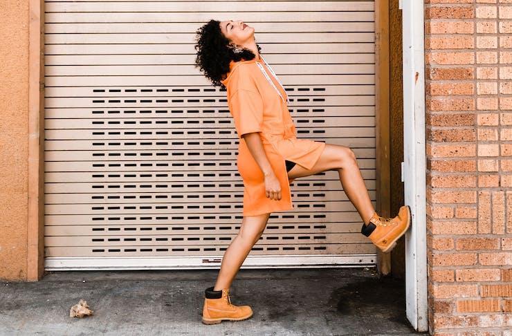 Woman in orange sweater jumper outside a garage door