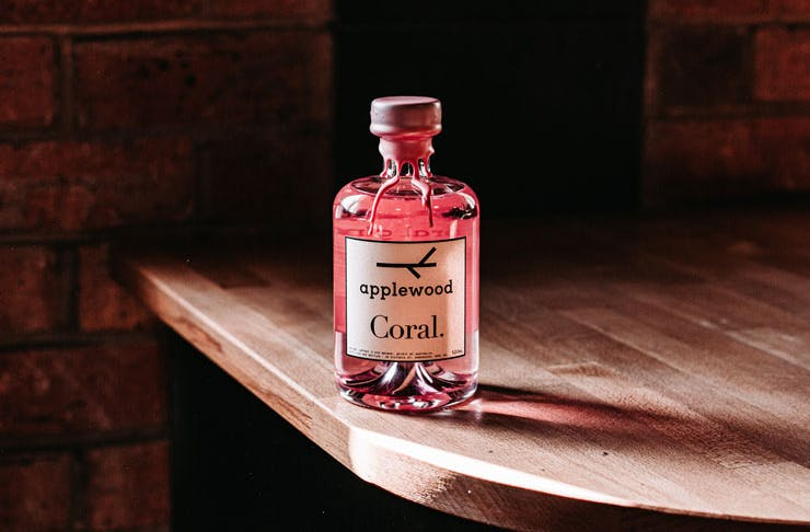 A bottle of Applewood's coral gin resting on a wooden table.