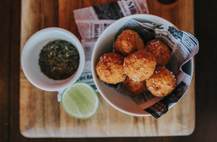 A bowl of arancini bowls sits on a wooden board with a small bowl of sauce.