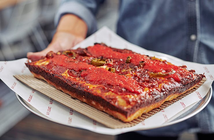 A deep dish pizza on a round plate covered in red sauce.