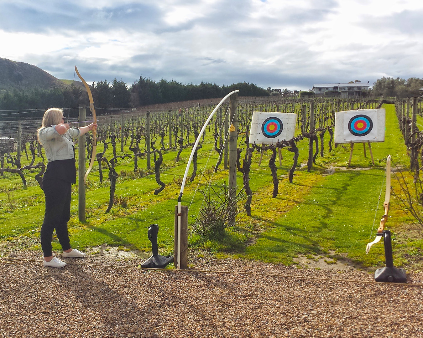 A girl takes aim with a bow and arrow at archery amongst the vines.