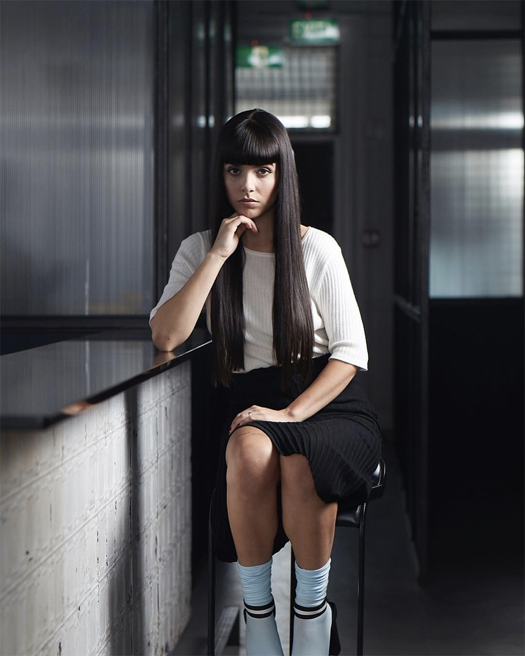 A woman sits on a stool with impeccably combed long dark hair.
