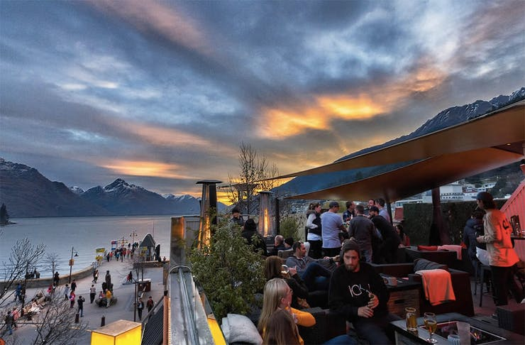 People frequent a beautiful rooftop bar in front of a stormy Queenstown sky.