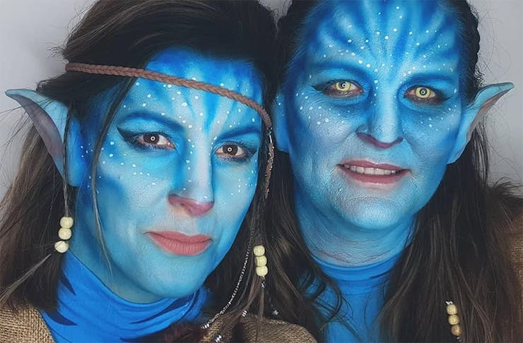 Two girls with painted faces looking like characters from Avatar.