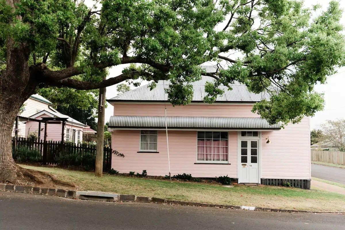 a pink cottage on a leafy street
