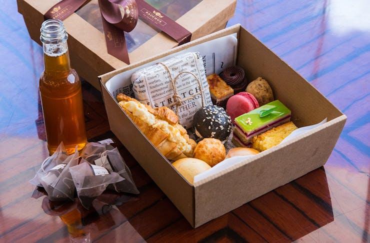 High tea treats in a cardboard takeaway box