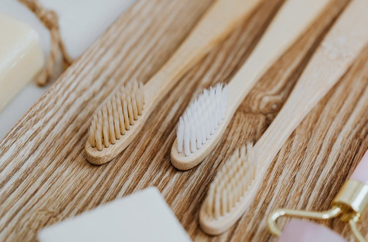 A close-up shot of three bamboo toothbrush heads.