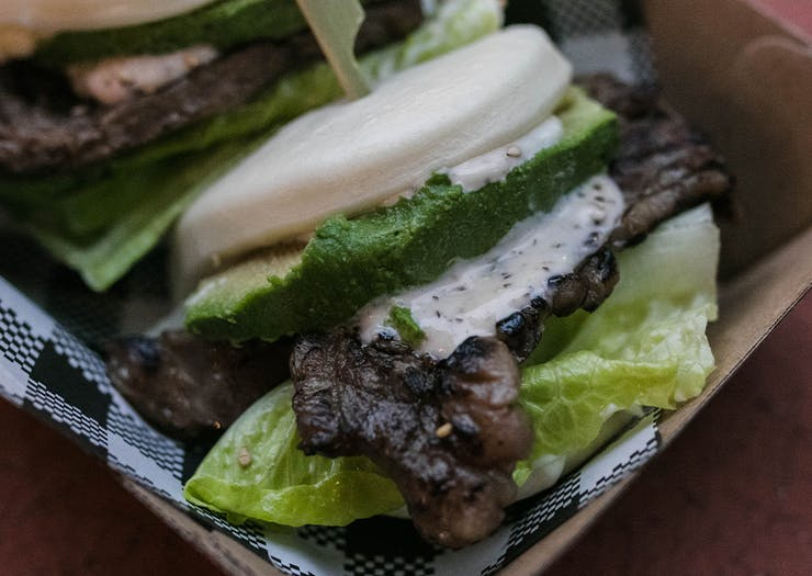 A close up of a beef short tip bao with lettuce and avocado