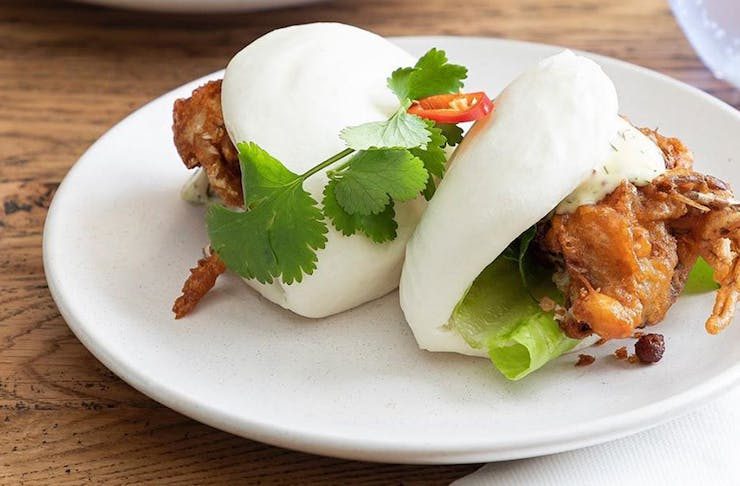 a plate with two crispy crab bao buns