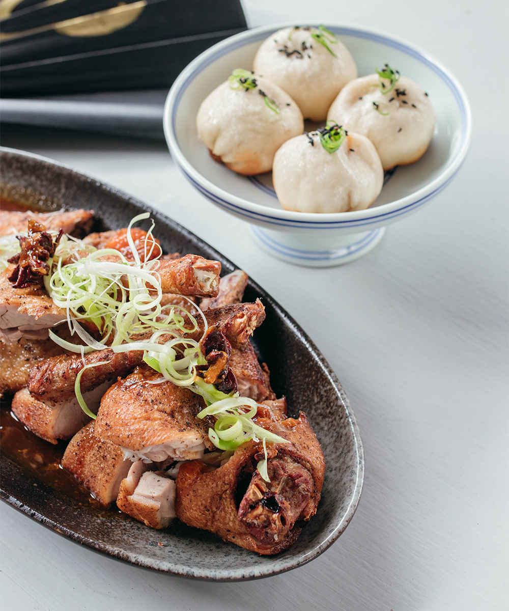 a plate of crispy fried duck pieces in front of a bowl of dumplings
