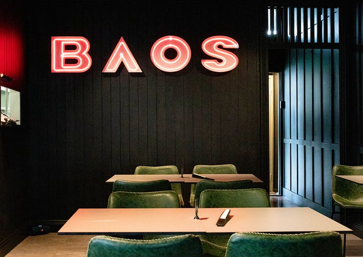 black interior at baos pop, with neon sign saying baos on the wall