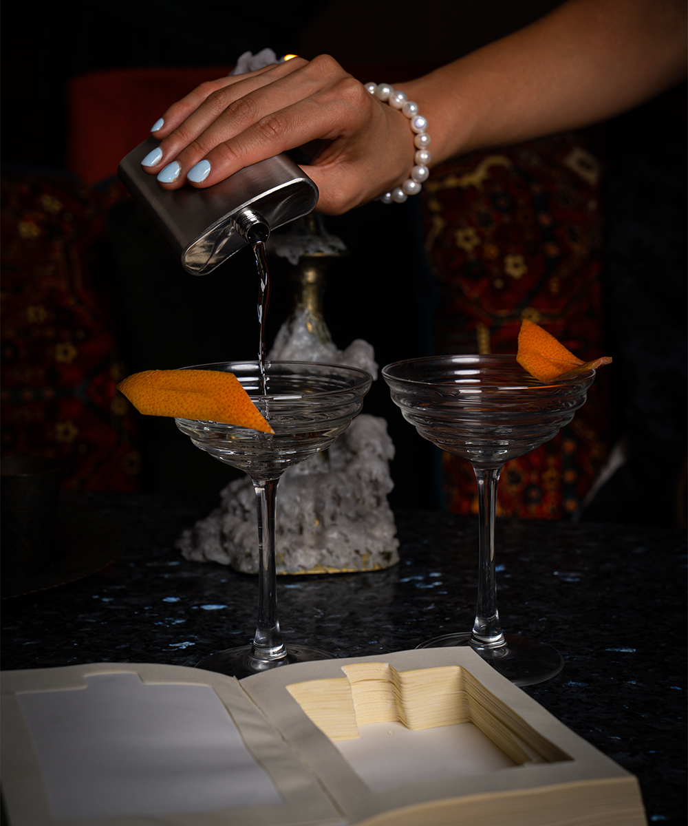 a cocktail being poured from a flask