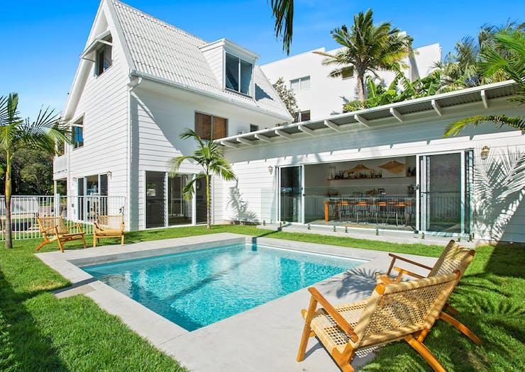 a white beach house with a pool