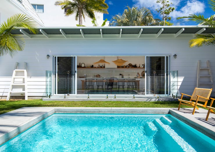 a white beach house with a pool in front of it