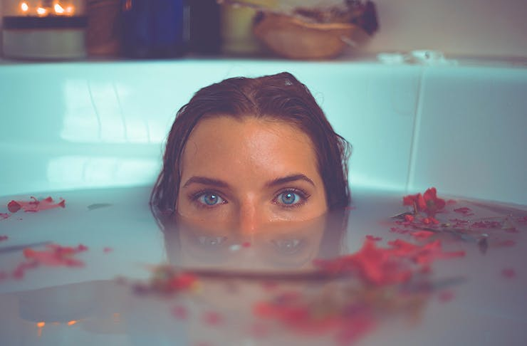 A woman sits in an almond milk bath with only her eyes showing above the waterline.