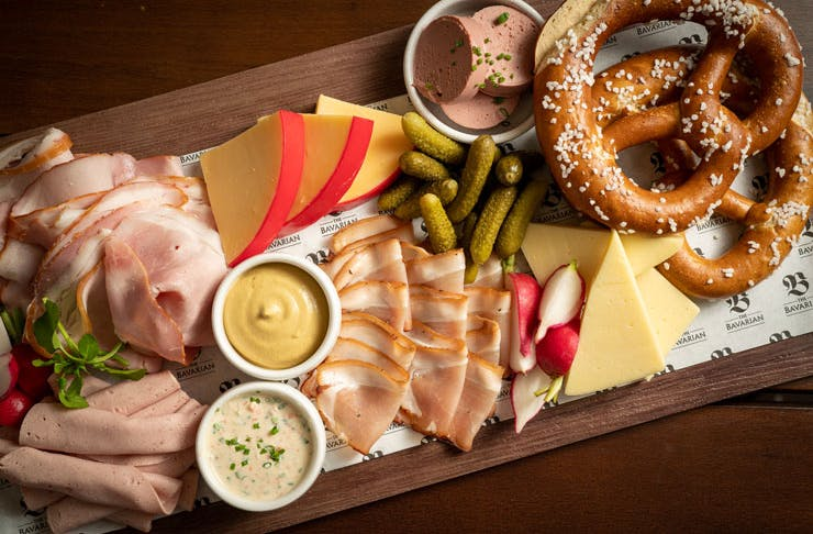 A Bavarian Bottomless Meat And Cheese Platter with pretzels.