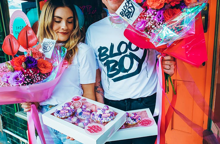 Two people holding colourful flowers and cakes.