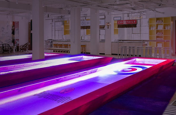 Two curling lanes illuminated at night.