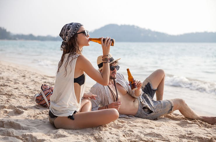 A couple sit on the beach drinking beers