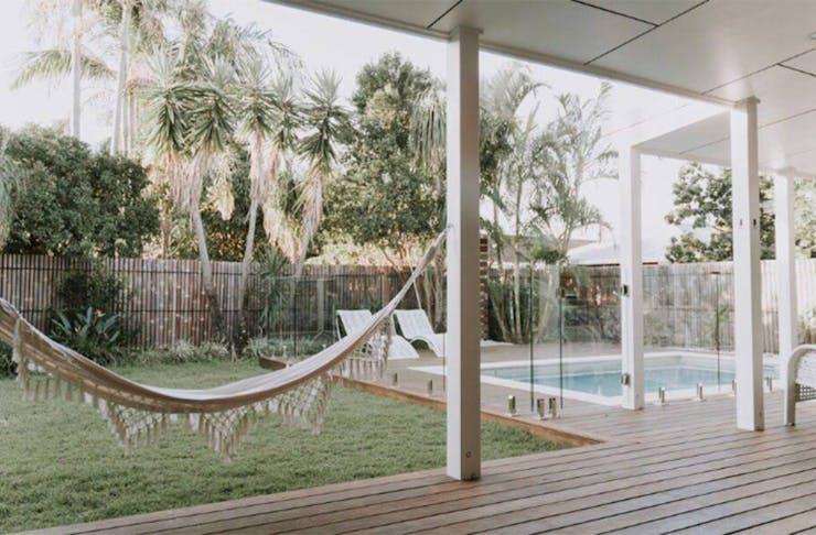a pool in a yard with a hammock