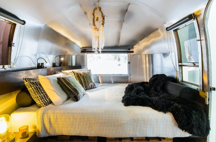 A made queen size bed inside a cosy Airstream in Noosa.