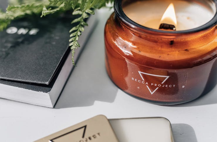 A diary with Becca project candle and balm spread on a white table.