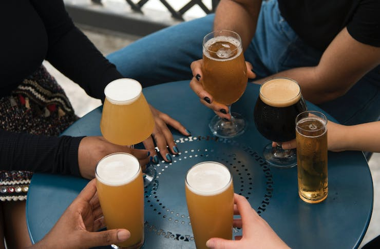 A group of people holding different types of beer handle