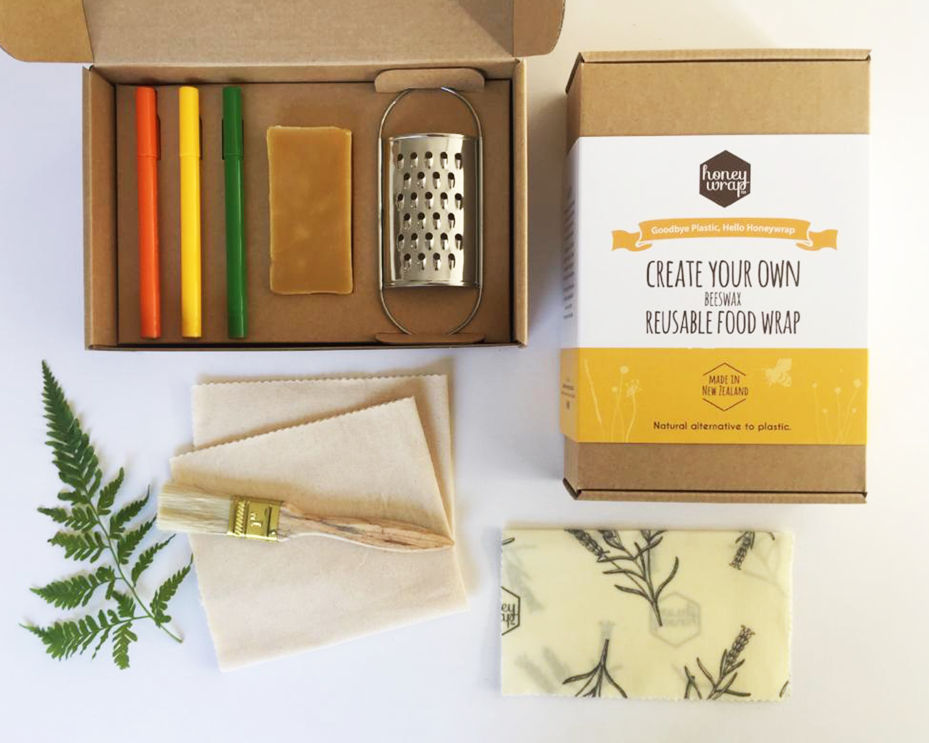 A wooden box with a mini grater, a bar of beeswax, folded pieces of material, felt tip pens, and a decorative fern leaf.