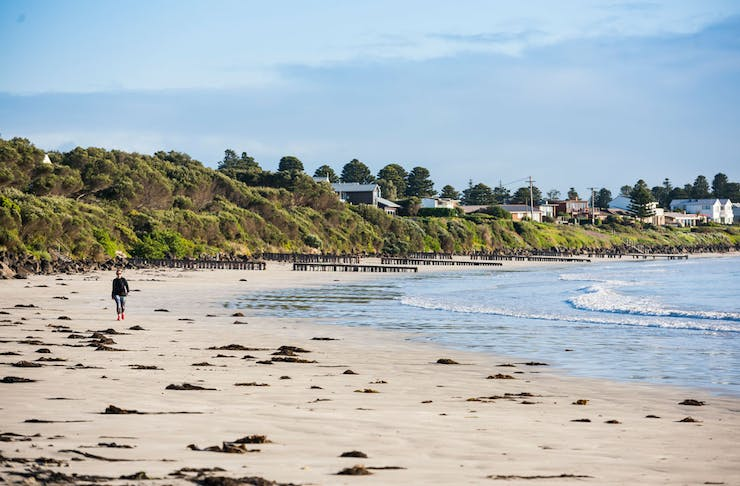 A person walks along the beach at Port Fairy, the town can be seen in the distance.