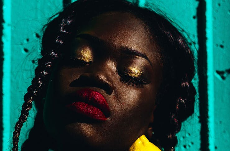 A woman wearing gold eye shadow and red lipstick.