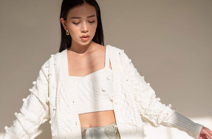 A model wearing a cream coloured For Love & Lemons cardigan.
