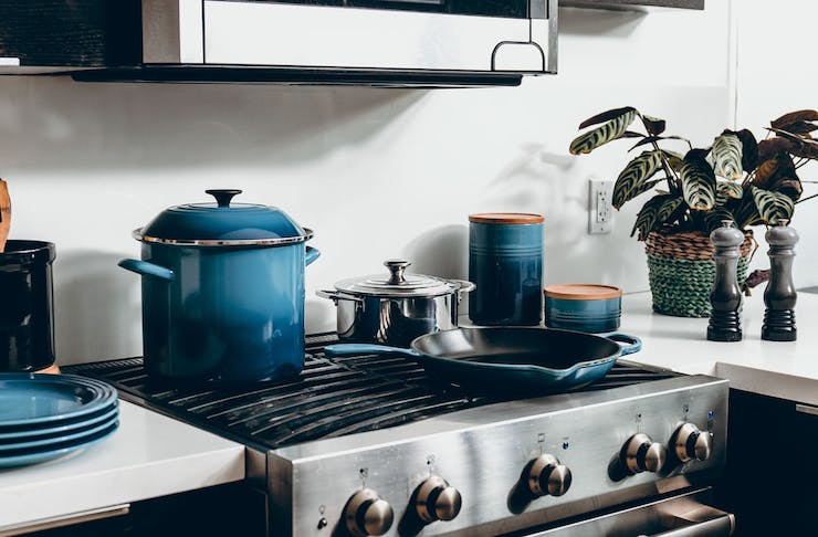 A range of blue cookware sitting on top of a gas cooktop in a beautiful kitchen.