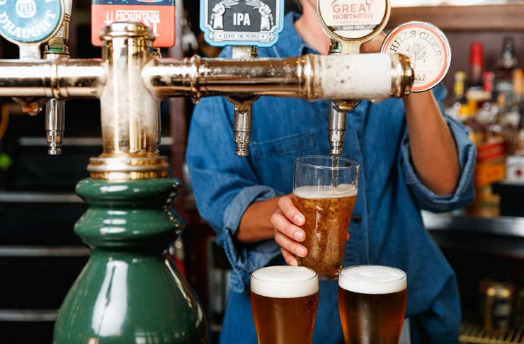 A bar person in a blue denim shirt pours schooners of beer from beer taps.