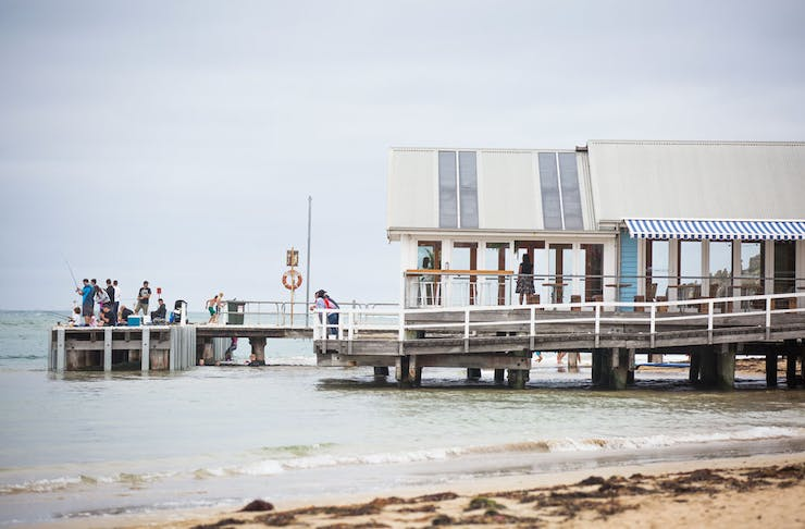 A group of people fishing off the pier at Barwon Heads.